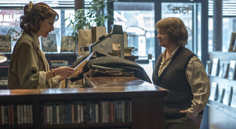 Still from Can You Ever Forgive Me?: Anna examines one of Lee's letters behind the bookstore counter as Lee looks on.