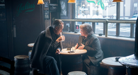 Still from Can You Ever Forgive Me?: Lee and Jack reunite in their bar, seated with drinks at a table in front of a window with a silence = death sticker on it.
