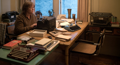 Still from Can You Ever Forgive Me?: Melissa McCarthy as Lee Israel, typing at her desk which is covered in typewriters and letter paper.