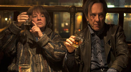 Still from Can You Ever Forgive Me?: Lee and Jack sit in a dark bar holding alcoholic drinks and indicating they want to order more.