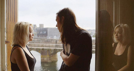 Milla and Leo look at each other in front of a window looking out over a body of water. Milla's reflection can be seen.
