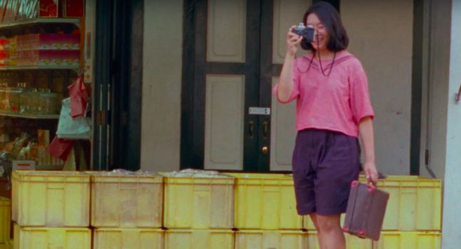 Shot of Sandi Tan as a teenager in Shirkers holding a camera up to her face to take a photograph.
