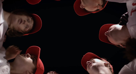 Joan (played by Bobbi Salvör Menuez) stands in a huddle with her teammates, filmed from below.  Multiple red baseball caps are visible.