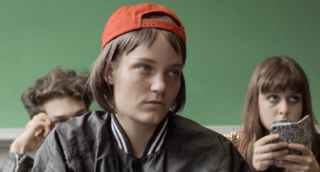 Still from I Remember Nothing: the first Joan (played by Audrey Turner) sits in a classroom looking disengaged, wearing her trademark red baseball cap.