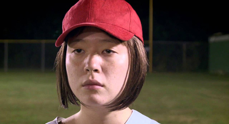 Another Joan (played by Adinah Dancyger) stands in the softball field looking slightly blank, wearing her red baseball cap.