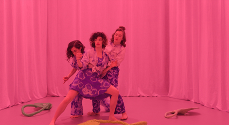 Video still from What Do Stones Smell Like in the Forest: The three-woman chorus in tye-die outfits interact with one another on a pink stage before a pink curtain, while their papier-maché masks lie on the stage.