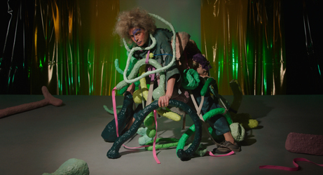 Video still from What do Stones Smell Like in the Forest: The golem looks at the camera as she leans on various green and pink papier-maché props that also cover her body. A shiny transparent green curtain is behind her.